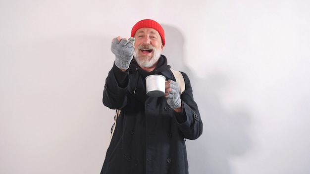 Cheerful homeless old man with a beard in a hat grinned holding money in his hand on an isolated background