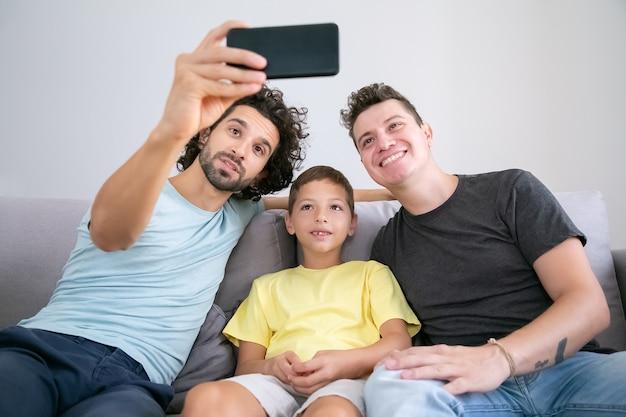 Allegri genitori omosessuali e bambino che prendono selfie al cellulare, seduto sul divano a casa, sorridendo alla telecamera frontale. vista frontale. famiglia e concetto di comunicazione