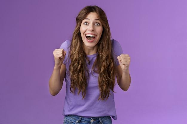 Allegro speranzoso carino fan femminile che celebra notizie fantastiche vincendo alla lotteria urla compiaciuto sorridenti ampiamente pompa pugno con gioia felicità successo trionfo posa sfondo viola