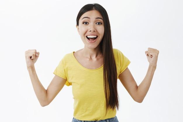 Femmina europea attraente allegra speranzosa e ottimista con capelli lunghi scuri che solleva allegramente il pugno di serraggio