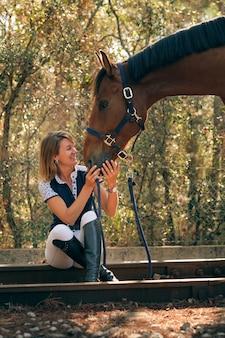 森の中で馬をなでる陽気な騎手