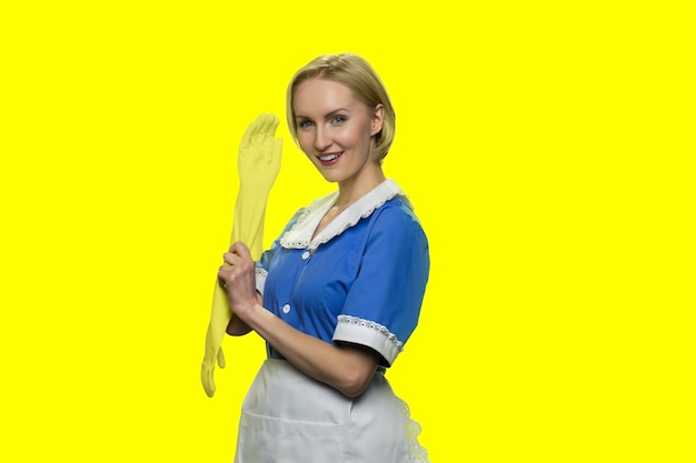Cheerful housemaid is putting on rubber gloves
