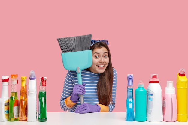 Cheerful housewife carries broom, smiles gladfully, wears striped sweater and headband, sits at desktop with laundry detergent and cleanser