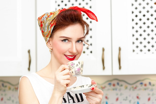 Cheerful housewife in a red kerchief in the kitchen