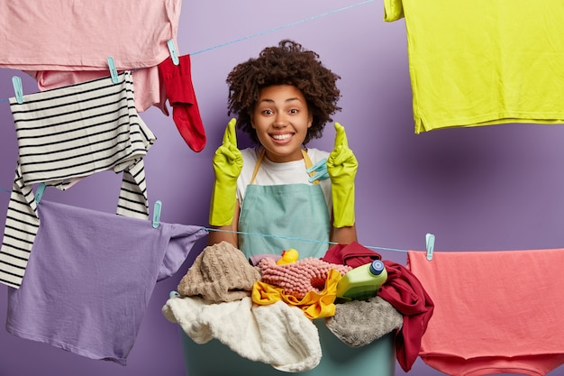 Cheerful housewife stands near laundry on clothesline, crosses fingers