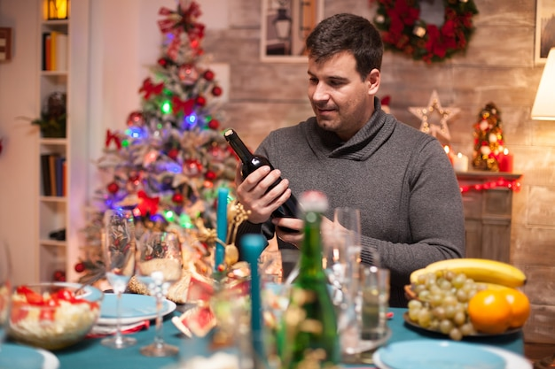 Cheerful husband looking at a bottle of wine for christmas family dinner sitting in front of the fireworks.