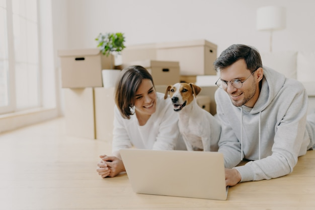 Cheerful husband and wife watch film online on laptop, rest on floor, relax and talk, their domestic animal poses between, relocate in new home, pose in spacious living room with unpacked boxes