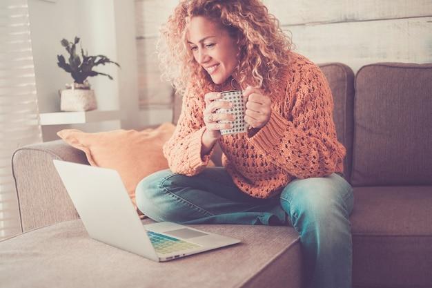 陽気な独立した大人の美しい女性が仕事をし、自宅でラップトップコンピューターを使用してソファに座ってコーヒーを飲みます