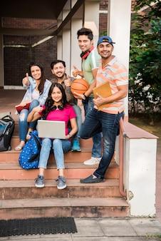 쾌활한 인도 아시아 젊은 대학생 또는 친구가 앉아, 서 있거나 캠퍼스에서 걷는 동안 함께 웃고 그룹