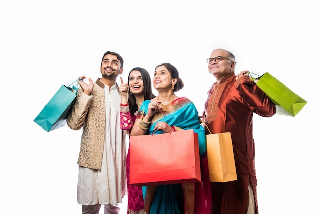 Веселая индийская семья делает покупки для фестиваля или свадьбы дивали, показывая красочные бумажные пакеты, изолированные на белом