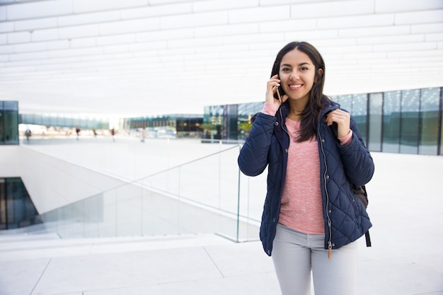 Cheerful indian student girl talking on mobile phone