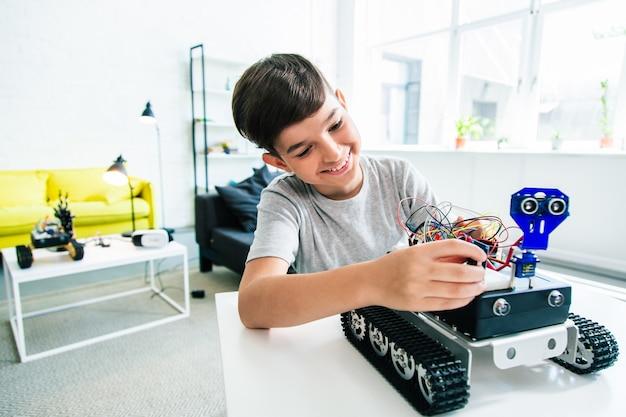 집에서 숙제를 하는 동안 로봇 장치를 만드는 명랑하고 독창적인 소년
