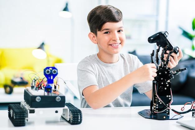 그의 엔지니어링 경이로움을 테스트하는 동안 리모콘을 들고 쾌활한 독창적 인 소년