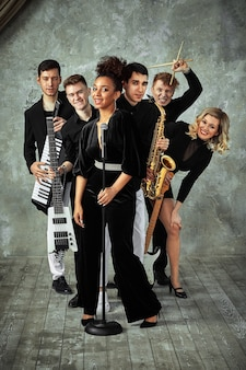Cheerful international music group on a gray wall, a group of musicians posing with various instruments, guitars, saxophone.