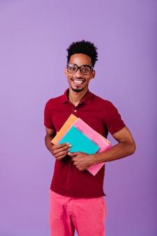 カラフルな教科書を持っている陽気な留学生。隔離された眼鏡で笑っているアフリカ人の屋内写真。