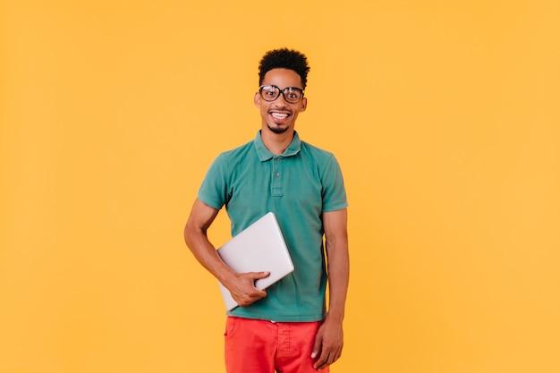 緑のtシャツの笑顔で陽気な留学生。ラップトップで興奮した男性のフリーランサーの肖像画。