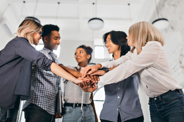 Cheerful international students with happy face expression going to work together on science project. indoor photo of blonde woman in trendy blouse holding hands with coworkers.