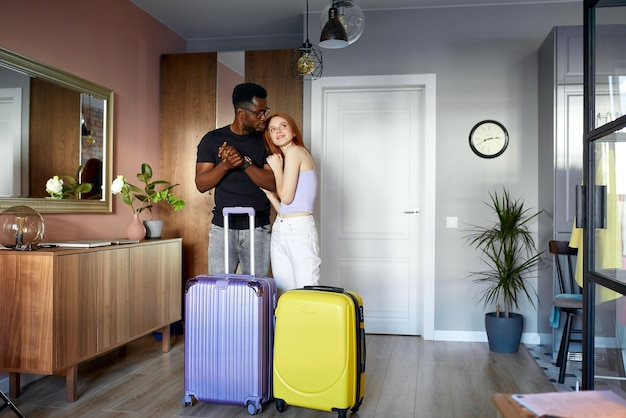 陽気な異人種間のカップルが新しいアパートに入る