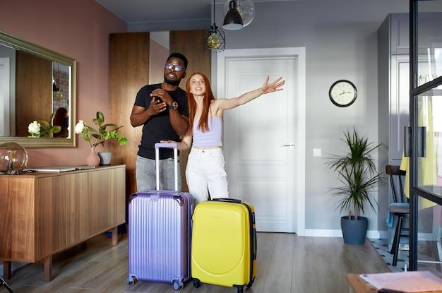 Веселая межрасовая пара входит в новую квартиру