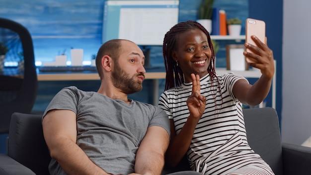 Веселая межрасовая пара фотографирует со смартфоном
