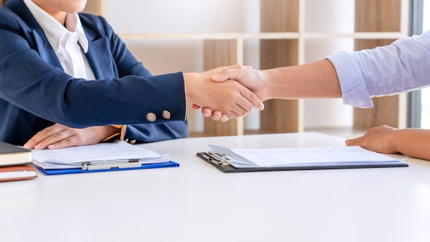 Cheerful interviewer hr manager welcoming women applicant at job interview handshaking