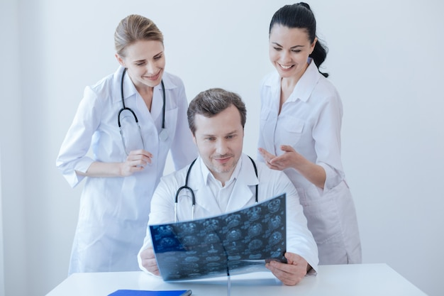 Cheerful involved qualified radiologists working and examining ct scan in the clinic while exchanging opinions