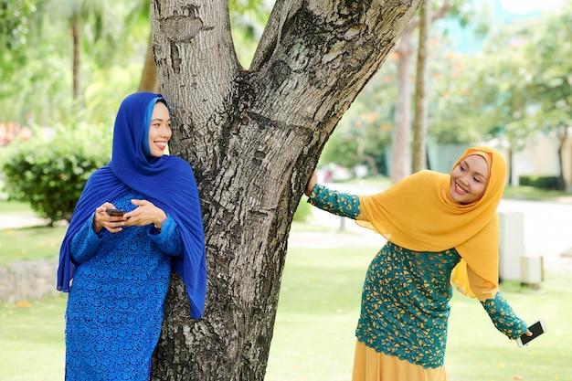 Cheerful islamic women playing in park