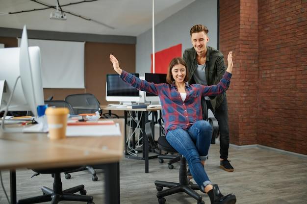 Веселые айтишники смотрят на монитор в офисе. веб-программист или дизайнер на рабочем месте, творческое занятие. современные информационные технологии, корпоративный коллектив
