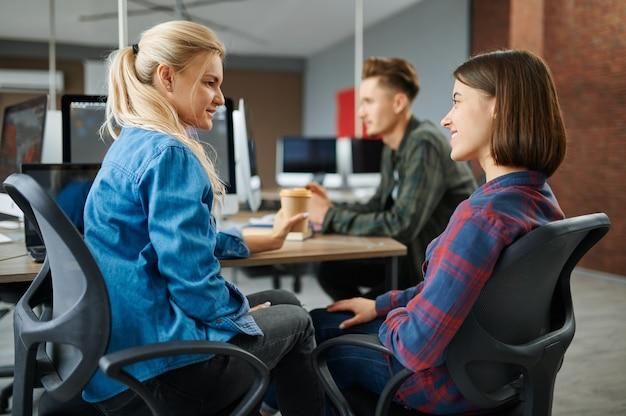 Веселые айтишники разговаривают в офисе, успешно работают. веб-программист или дизайнер на рабочем месте, творческое занятие. современные информационные технологии, корпоративная команда