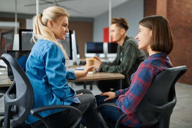 Cheerful it specialists talking in office, success work. web programmer or designer at workplace, creative occupation. modern information technology, corporate team