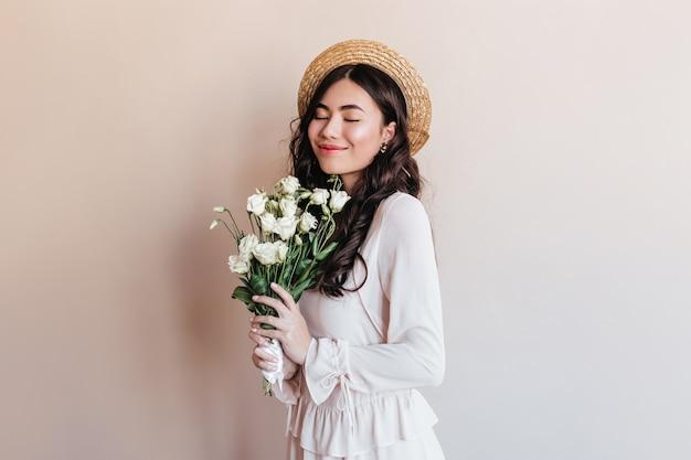 花を持っている陽気な日本人女性。花束と麦わら帽子でスタイリッシュなアジアのモデルのスタジオショット。