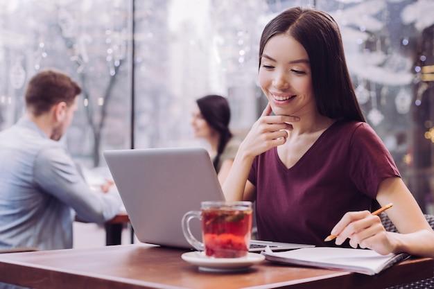Веселая веселая студентка трогает ее лицо, глядя на экран и улыбаясь