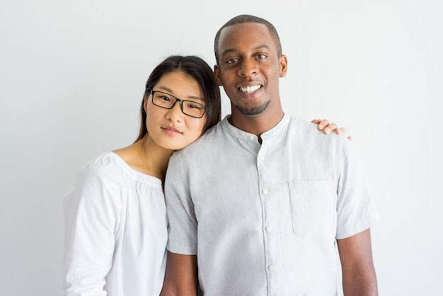 Cheerful jolly young interracial couple looking at camera.