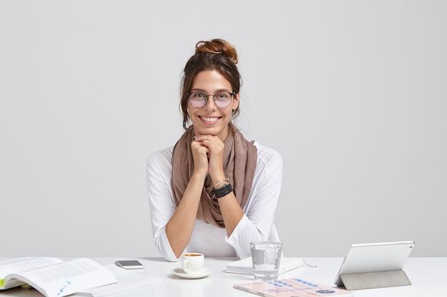 Веселая журналистка с приятной внешностью, в прозрачных очках, с темными волосами причесана, обогащает знания во время чтения, с нежной улыбкой сидит на рабочем месте с тачпадом, стаканом воды