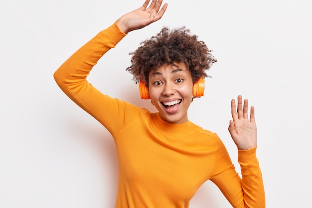 Cheerful joyful african american woman enjoys awesome sound quality wears stereo wireless headphones listens favorite music dances with rhythm dressed in orange jumper isolated on white wall