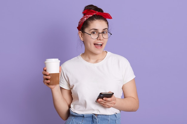 Cheerful joyful european female in white casual t shirt and red hairband, holding take-away coffee and browsing internet in mobile phone, texting friend,