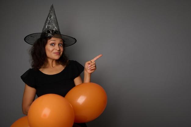 黒に身を包んだ、ウィザードの帽子をかぶった陽気な楽しい幸せなヒスパニック系の女性は、オレンジ色の膨らんだ気球を保持し、灰色の背景のコピースペースを指しています。ハロウィーンパーティーのコンセプト