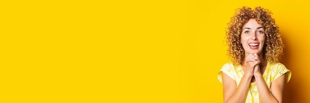 黄色の背景に陽気なうれしそうな驚きの縮れ毛の若い女性