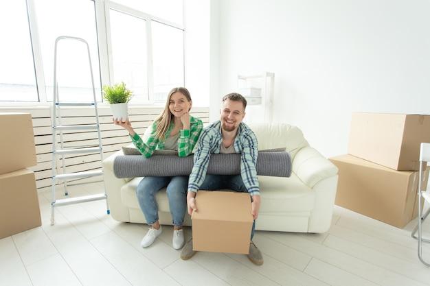 Веселая радостная молодая пара, очаровательная девушка и красавец, держащий коробку с вещами и горшок с