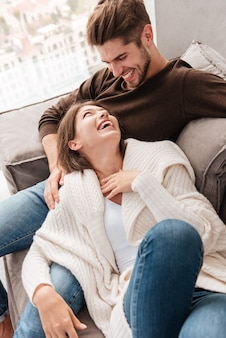 Cheerful joyful young couple sitting and laughing on couch at home
