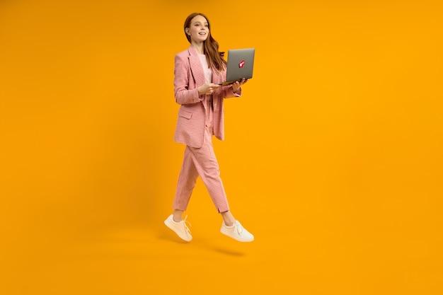黄色のスタジオの背景に分離されたラップトップを持つ陽気なジャンプ女性現代技術の自由...