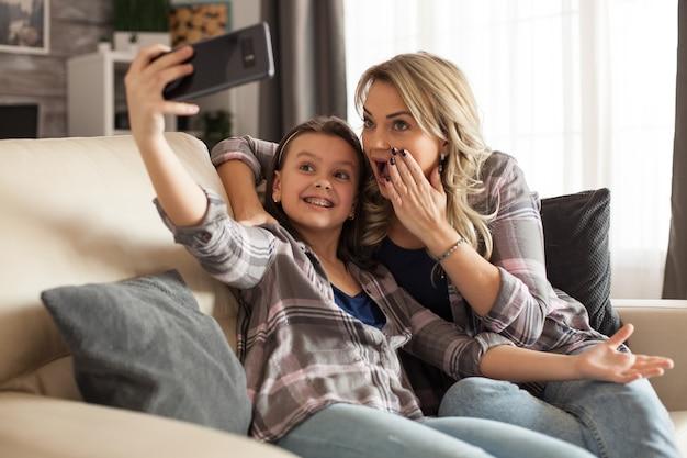 陽気な子供と彼女の母親は、楽しい時間を過ごしてソファに座っているリビングルームで自分撮りをしています。