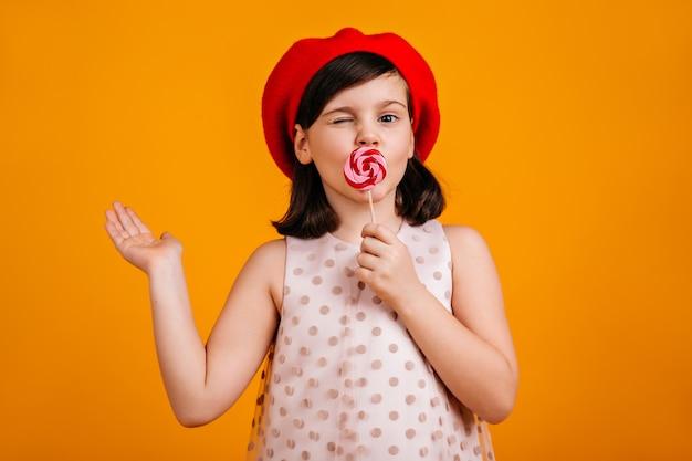 ロリポップを食べる陽気な子供。黄色に分離されたキャンディーを持つ短い髪のプレティーンの女の子。