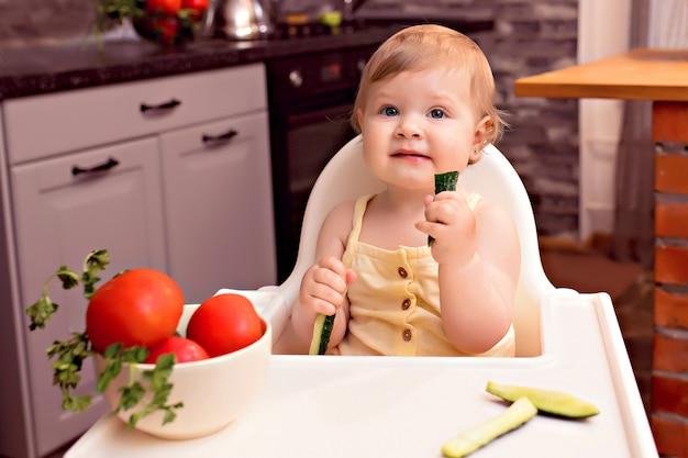 Веселый малыш ест овощи. портрет счастливая девушка в стульчике на кухне