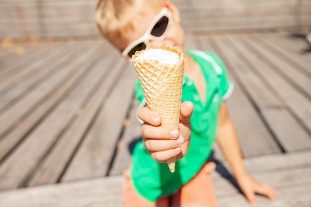 アイスクリームコーンを示すサングラスの陽気な子供