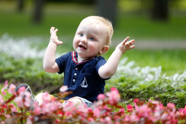 잔디 위의 쾌활한 아이가 손뼉을 친다