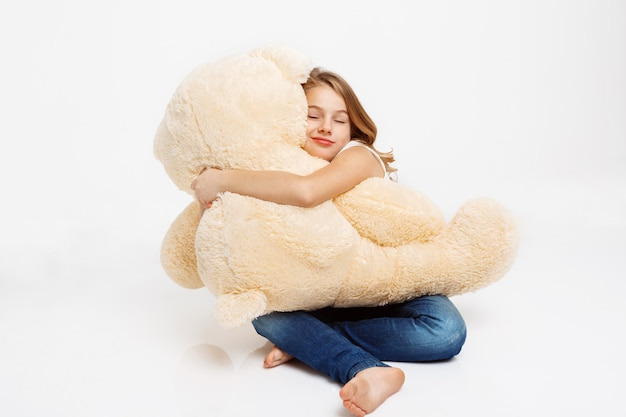 Cheerful kid sitting on floor holding toy bear on knees.