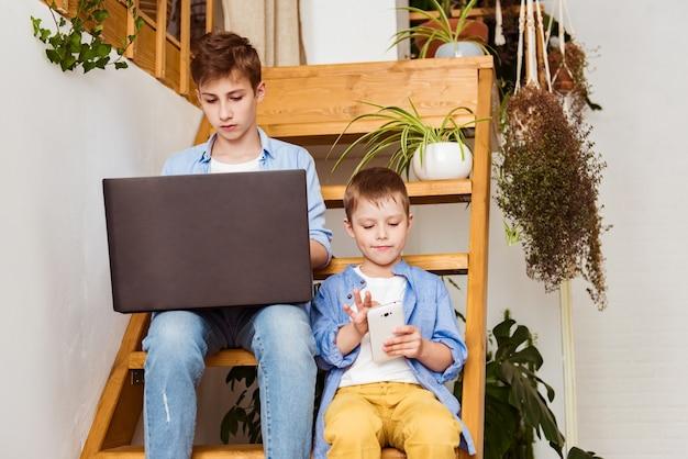 평상복을 입은 쾌활한 아이들이 집에서 계단에 앉아있는 동안 가제트를 사용하고 있습니다.