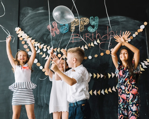 Cheerful kids releasing balloons on birthday party
