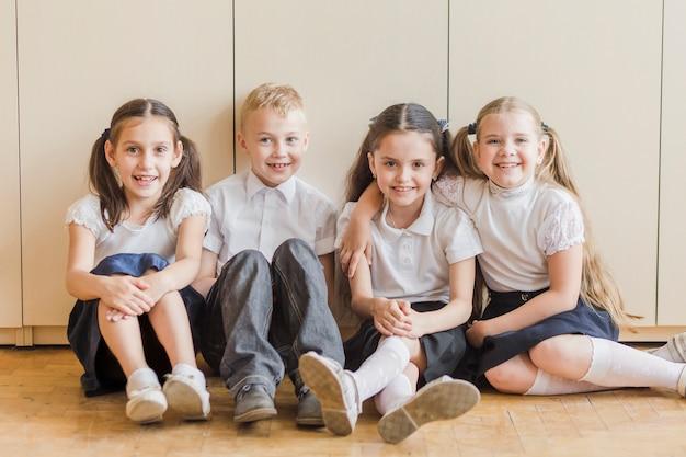 Cheerful kids sitting on floor at school